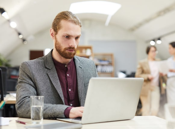 Picture of a person working on a laptop in an office